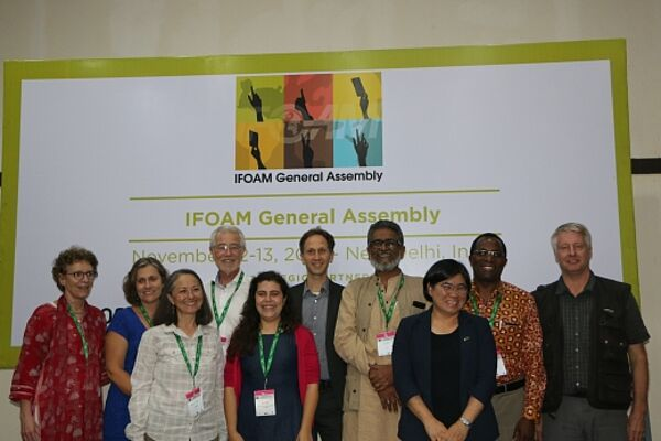 10 people in front of the IFOAM General Assembly poster.