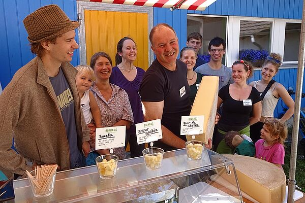 Alfred Schädeli with a piece of fresh cheese surrounded by people.