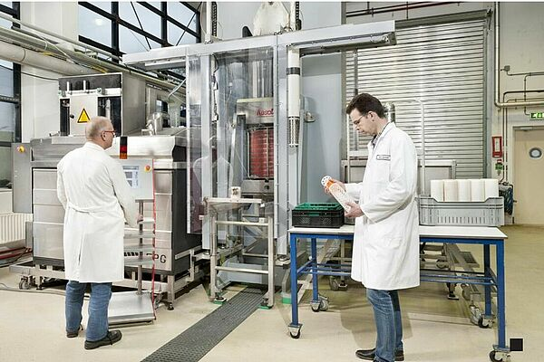 2 people stand in front of a high pressure machine