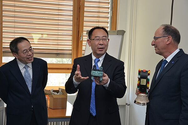 Three men standing, two of them are exchanging gifts (a small Chinese pot and a Swiss cow bell).