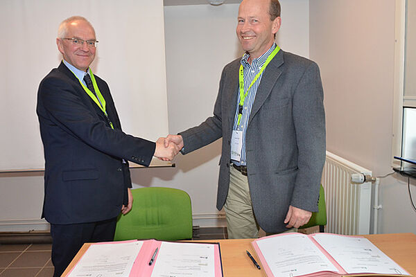 Two men are shaking each other's hands and smiling. In front of them, there are two signed documents on a table.