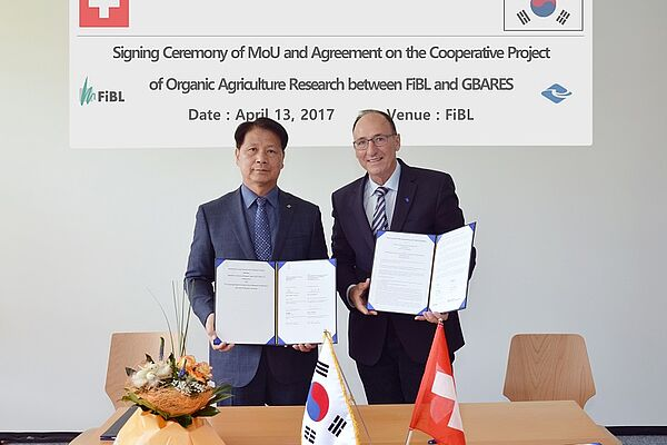 2 men stand at a table and present the signed agreements. THe table is decorated with a Swiss and a South Korean flag as well as some flowers.